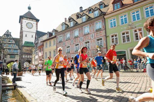 """Hindurch durch das Schwabentor laufen die Sportlerinnen und Sportler beim """"Mein Freiburg-Marathon"""".   Fotos: FWTM/Schönenf Foto: Die Oberbadische"""