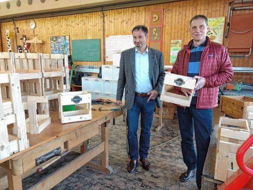 """Kooperationspartner: Joachim Trüby und Thomas Hein (von links) mit einigen der Kisten, die das St. Josefshaus in seinen Werkstätten für die Brauerei """"Markgräfler Brauwerk"""" in Tannenkirch herstellt.       Foto: zVg Foto: Weiler Zeitung"""