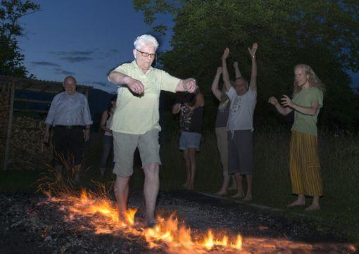 Heiße Sohlen: Elisabeth Netzer läuft über die acht Meter lange Feuerspur. Im Hintergrund freuen sich Erwin Lang (l.) und weitere Seminarteilnehmer mit ihr. Foto: zVg Foto: zVg