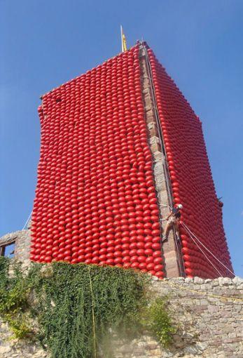 Ein Kletterer befestigt die roten Ballons am Turm.   Foto: Dorothea Gebauer Foto: Die Oberbadische