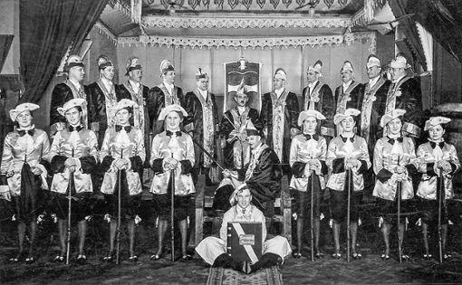 """Das Foto, aufgenommen bei der ersten Prunksitzung (heute: Zunftabend) im Jahr 1939 zeigt den Elferrat der Narrenzunft """"D'Rhiischnooge"""" Neuenburg am Rhein mit dem damaligen Zunftmeister Franz Homburger und die neu gegründete Zunftgarde, die bei ihrem Einzug """"stürmisch gefeiert wurde"""". Foto: zVg/Archiv Narrenzunft """"D'Rhiischnooge"""""""