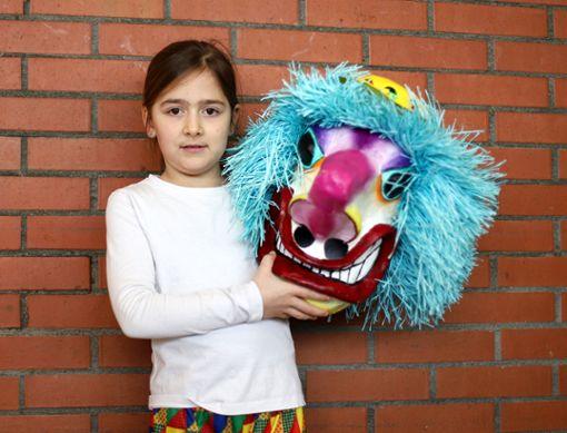 """Coralie (8 Jahre): """"Meine Oma hatte die Waggis-Maske über Fasnacht immer als Dekoration im Blumenladen stehen. Weil sie jetzt in Rente ist, durfte ich sie heute anziehen."""" Foto: Kristoff Meller Foto: Kristoff Meller"""