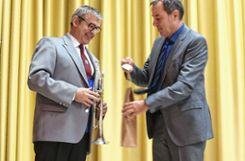 Bürgermeister Andreas Schneucker (r.) übergibt Stephan Jourdan, Dirigent des Binzener Musikvereins, ein Weinpräsent. Foto: Alexandra Günzschel
