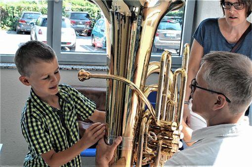 Einmal kräftig pusten bitte: Der achtjährige Timo testet die Basstuba an,  Instrumentenlehrer Ingo Ganter gibt erste Tipps.      Foto: Ines Bode Foto: Markgräfler Tagblatt