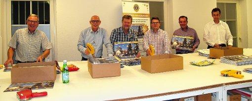 Mitglieder des Lions Clubs  Schliengen beim Bekleben der Glücks-Adventskalender    Foto: zVg Foto: Weiler Zeitung