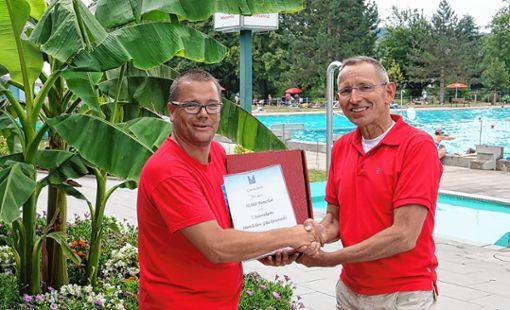 Schwimmmeister Manuel Gutmann (links) gratuliert dem 50000. Badegast,  Fank Philipp.     Foto: Hans-Jürgen Hege Foto: Markgräfler Tagblatt