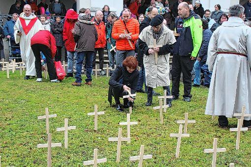 Auch Sozialamtsleiterin Cornelia Roesner und die Degerfelder Ortsvorsteherin Karin-Reichert-Moser stellten   am Gedenkstein Kreuze  auf.  Foto: Rolf Reißmann Foto: Die Oberbadische