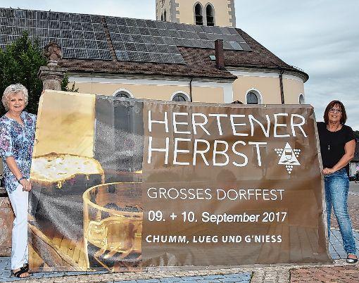 """Kornelia Wehrle (links)  und Anita Basso vom Verein """"Dorfkultur Herten"""" präsentieren den Banner für das Dorffest am 9. und 10. September.   Foto: Heinz Vollmar Foto: Die Oberbadische"""