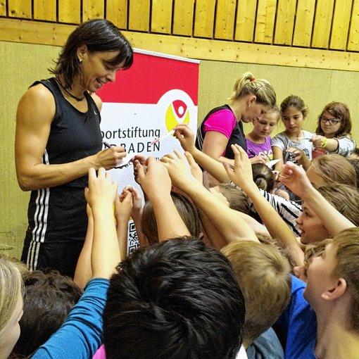 Nicole Grether (links) und Charmaine Reid schreiben auf ihrer Tour durch die hiesigen Schulen fleißig Autogramme.   Foto: zVg Foto: Die Oberbadische
