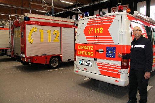 feuerwehrmann Stefan Kirn vor den mit dem neuen Logo ausgestatteten Feuerwehrautos   Foto: Reinhold Utke Foto: Weiler Zeitung