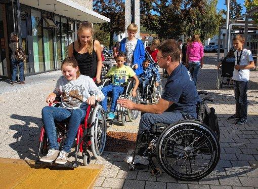 Gar nicht so einfach war es für die Oberrhein-Gymnasiasten,  mit einem Rollstuhl  über  eine kleine  Rampe zu fahren.  Marcel Langensieper gibt dazu entsprechende   Tipps, wie das Hindernis gemeistert werden kann.     Foto: dz Foto: Weiler Zeitung