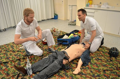 Jeder Handgriff muss sitzen: Andreas Haug (links) und Moreno Futterer widmen sich konzentriert dem elektronischen Patienten am Boden. Die beiden Mediziner haben sich noch nie zuvor gesehen.   Fotos: Adrian Steineck Foto: Die Oberbadische