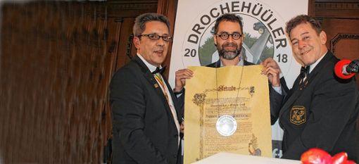 Peter Quercher (l.) und Andreas Glattacker (r.) überreichen  Ulrich Hoehler den Drochehüüler-Orden.   Fotos: Gerd Lustig Foto: Die Oberbadische