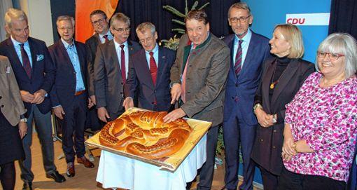 Umringt von Mandats- und Funktionsträgern der Partei schnitt CDU-Kreisvorsitzender Jürgen Rausch die Neujahrsbrezel an, rechts neben Rausch der Bundestagsabgeordnete Armin Schuster. Foto: Peter Ade